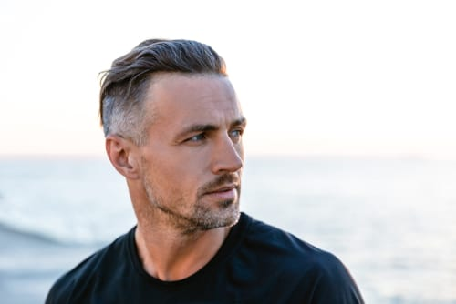 close-up portrait of handsome adult man with grey hair looking away on seashore-img-blog
