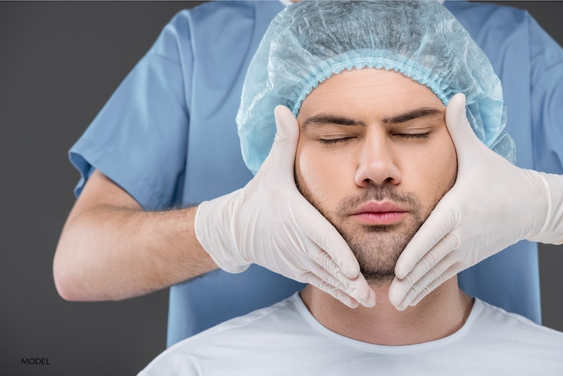 Man preparing for surgery with his surgeon's hands surrounding his face.