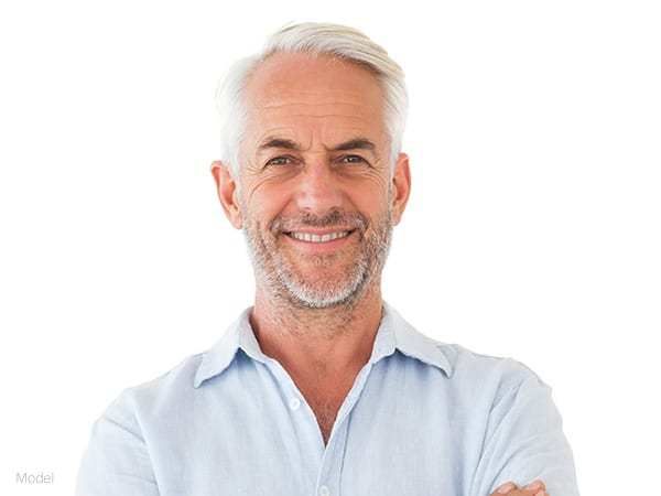 male model facing forward with gray hair and beard, wearing a white polo shirt for stemcell enhancement facelift